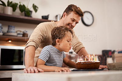Buy stock photo Shot of a boy blowing out the candles on his birthday cake while celebrating with his dad