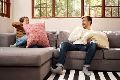 Buy stock photo Shot of a man and his young son having a pillow fight on the sofa at home