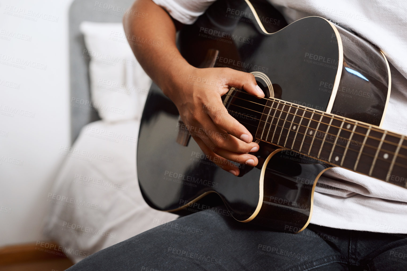Buy stock photo Shot of a young man playing the guitar while sitting at home