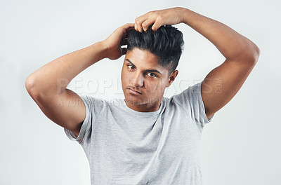 Buy stock photo Studio shot of a young man putting his fingers through his hair