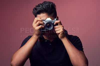 Buy stock photo Studio shot of a young man holding up a camera