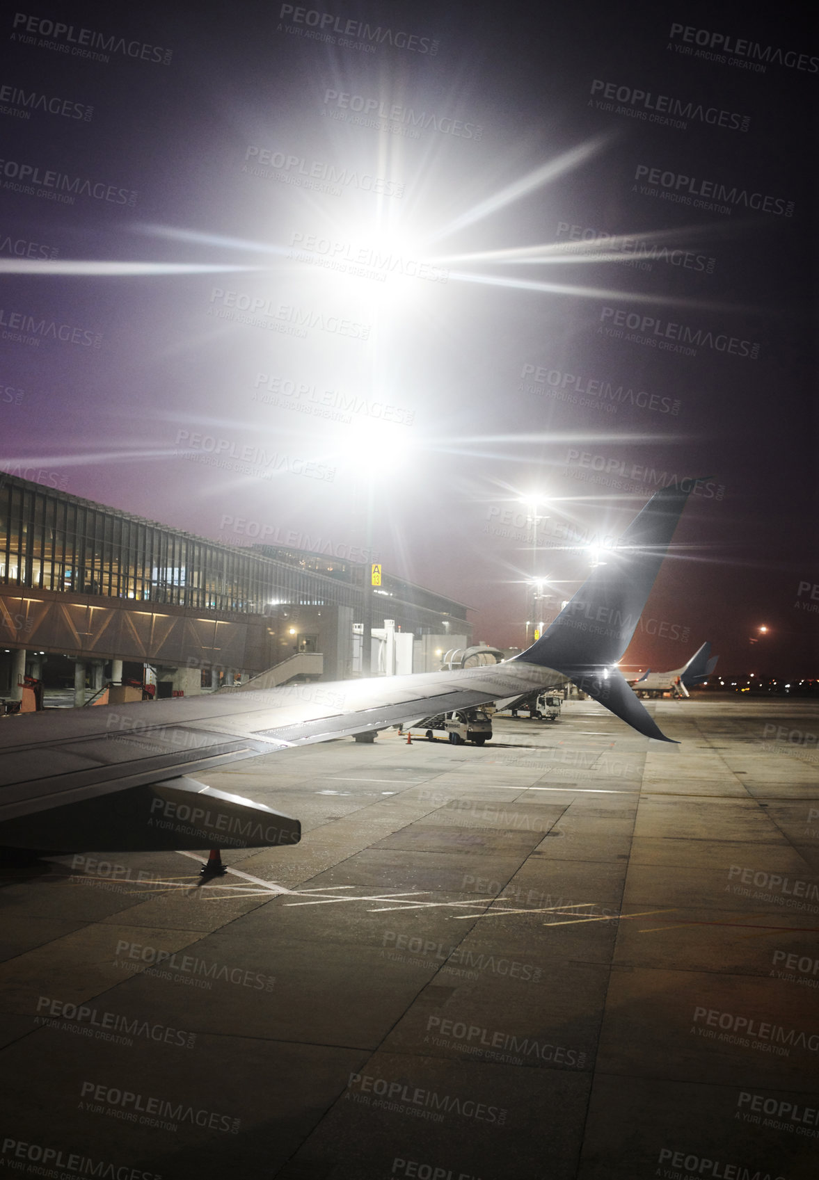 Buy stock photo Shot of airplanes at a modern airport during the night