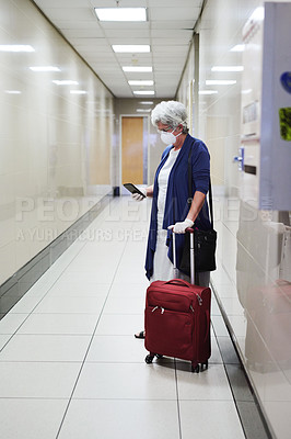 Buy stock photo Shot of a senior woman wearing a mask and using a smartphone in an airport