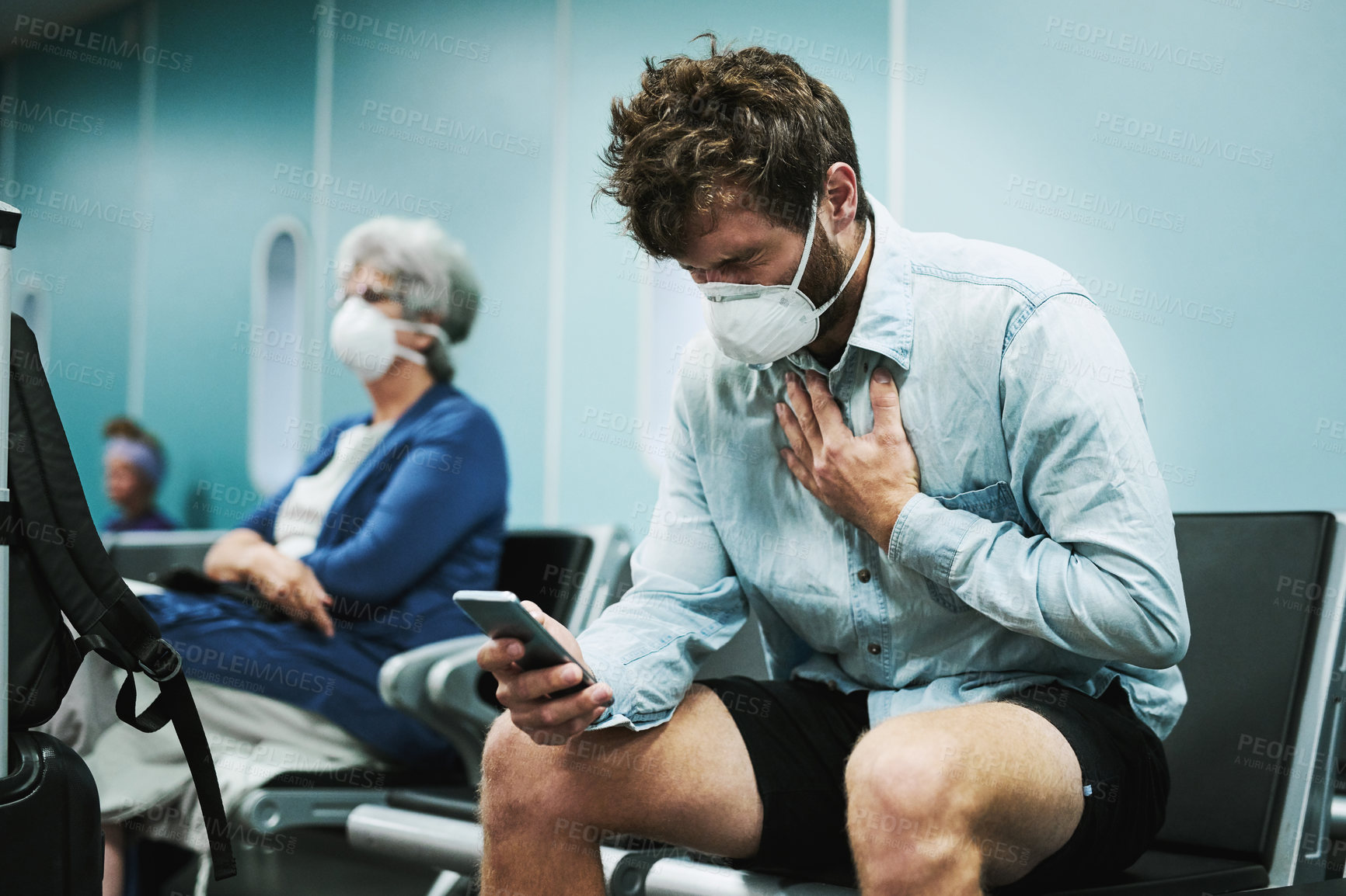 Buy stock photo Shot of a masked young man using a smartphone while experiencing chest pain in an airport waiting area