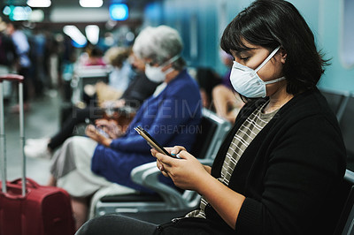 Buy stock photo Shot of a young woman wearing a mask and using a smartphone in an airport waiting area