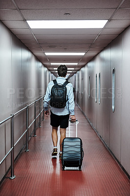 Buy stock photo Rearview shot of a young man waking through an airport with his luggage