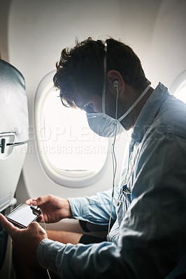 Buy stock photo Shot of a young man wearing a mask and using a smartphone with earphones in an airplane