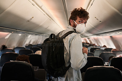 Buy stock photo Shot of a young man wearing a mask and boarding an airplane