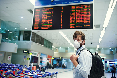 Buy stock photo Shot of a young man wearing a mask in an airport