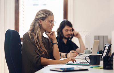 Buy stock photo Shot of a young businesswoman working in an office with her colleague in the background