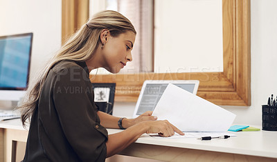 Buy stock photo Shot of a young businesswoman going through paperwork in an office