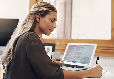 Buy stock photo Shot of a young businesswoman going through paperwork while using a laptop in an office