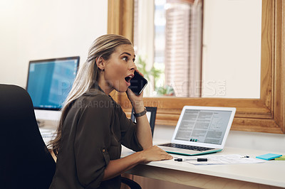 Buy stock photo Shot of a young businesswoman looking surprised while talking on a cellphone in an office