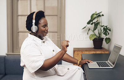 Buy stock photo Shot of a young businesswoman using headphones and a laptop in an office