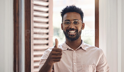 Buy stock photo Portrait of a young businessman showing thumbs in an office