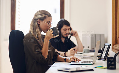 Buy stock photo Shot of a young businesswoman working on a laptop in an office with her colleague in the background