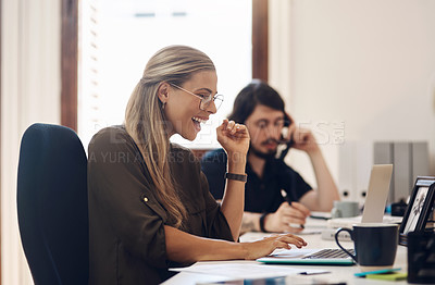 Buy stock photo Shot of a young businesswoman looking excited while working on a laptop in an office