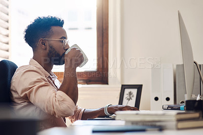 Buy stock photo Shot of a young businessman drinking coffee while working on a computer in an office