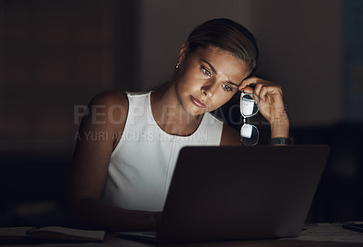 Buy stock photo Shot of a young businesswoman looking worn out while using a laptop during a late night at work