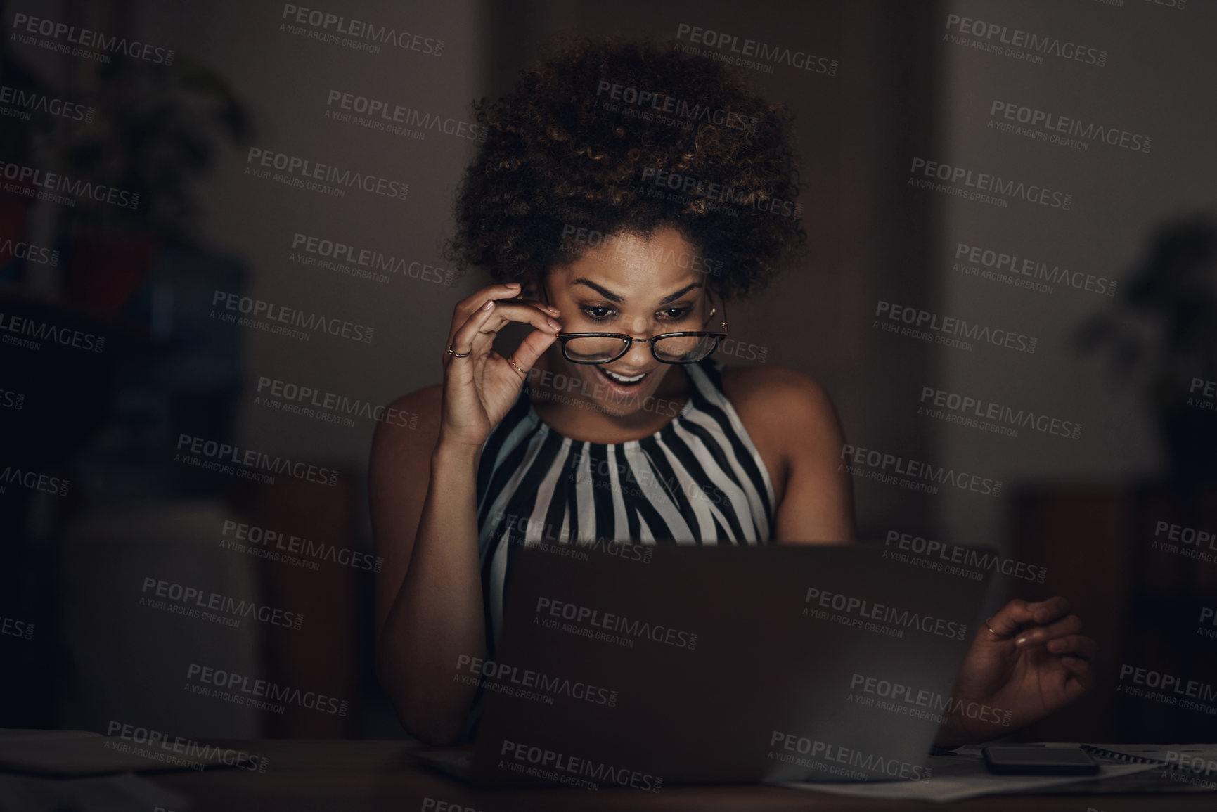 Buy stock photo Shot of a young businesswoman using a laptop and looking surprised during a late night at work
