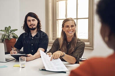Buy stock photo Shot of a group of businesspeople going through paperwork during a meeting in an office
