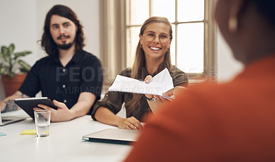 Buy stock photo Shot of businesspeople passing paperwork during a meeting in an office