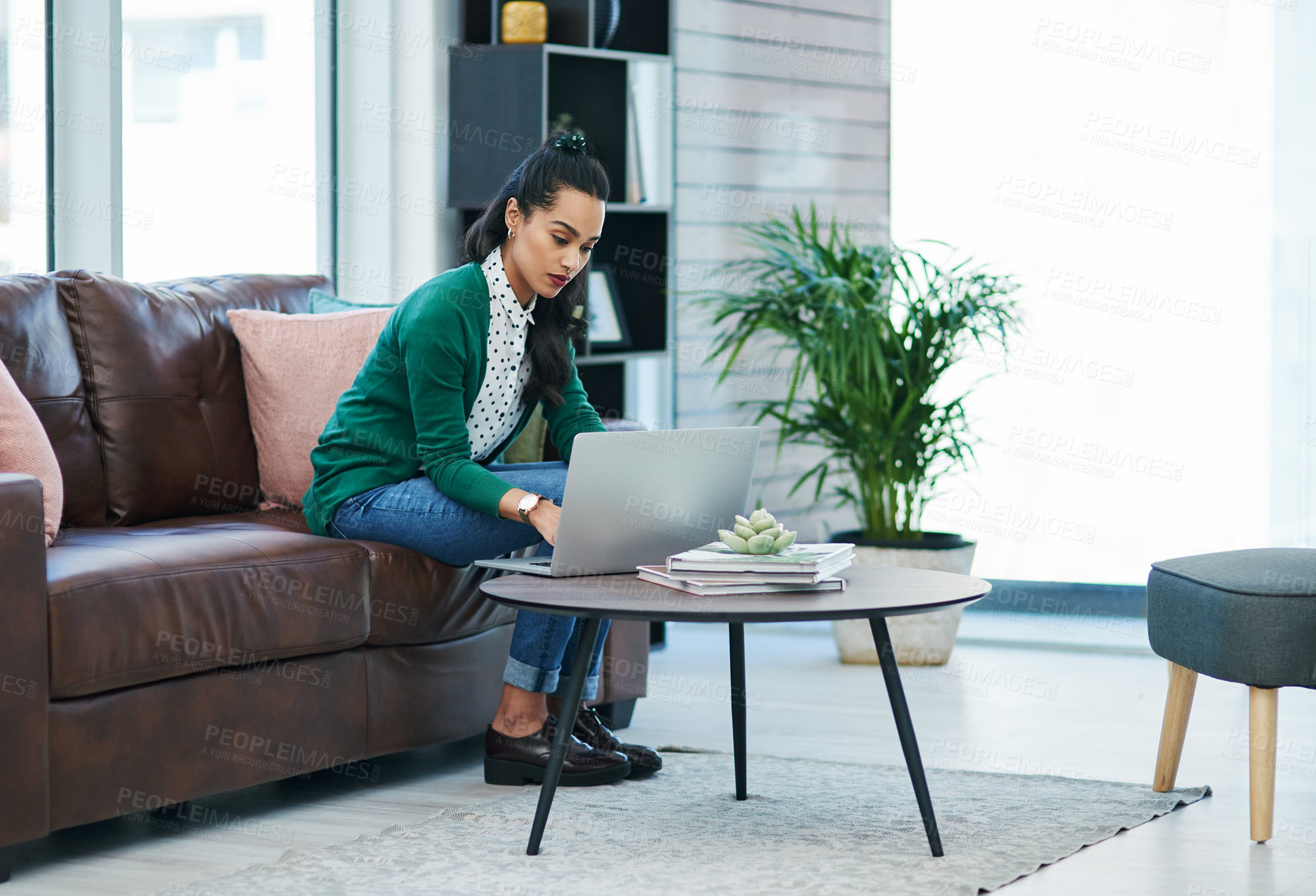Buy stock photo Shot of a young woman using a laptop while relaxing on a sofa