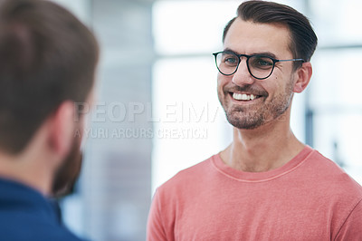 Buy stock photo Shot of two young businessmen having a conversation in a modern office