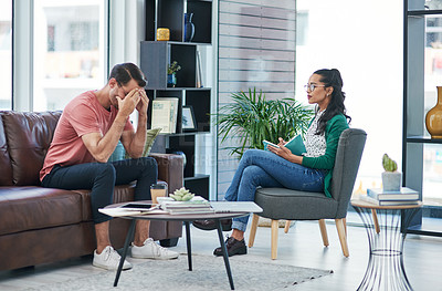 Buy stock photo Shot of a young man crying while having a discussion with a woman in a modern office