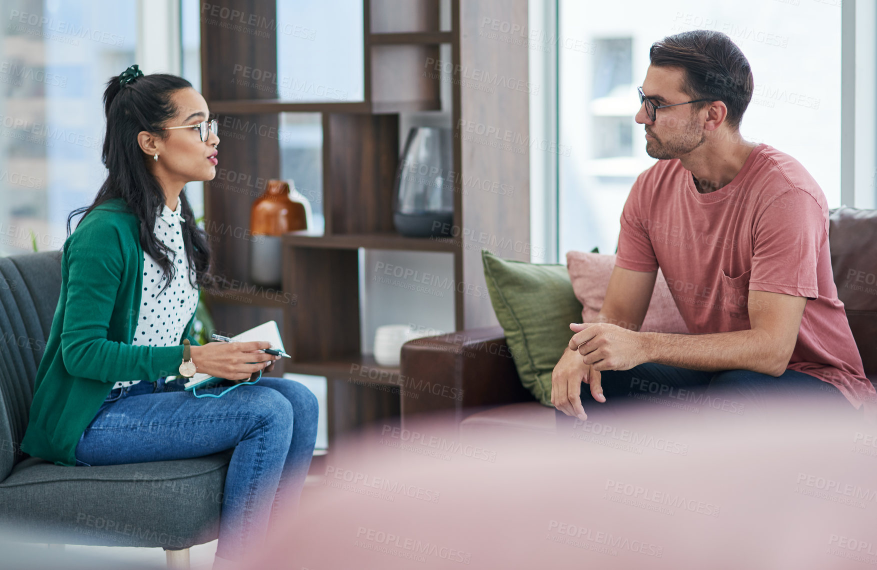 Buy stock photo Shot of a young man and woman having a discussion in a modern office