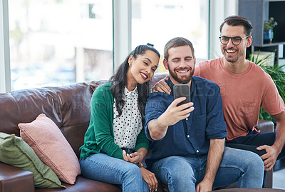 Buy stock photo Shot of two young men and a woman taking selfies together on a sofa