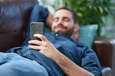 Buy stock photo Shot of a young man using a smartphone while relaxing on a sofa