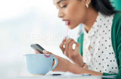Buy stock photo Shot of a young businesswoman applying lipstick using a smartphone with a smudge of it on a cup at work