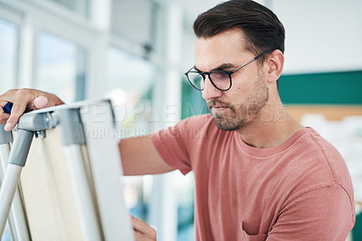 Buy stock photo Shot of a young businessman using a whiteboard during a brainstorming session in a modern office