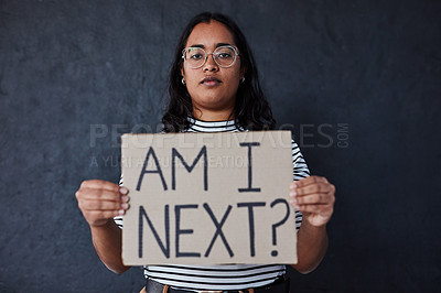 Buy stock photo Studio shot of a young woman protesting against gender based violence against a dark background