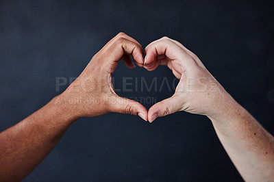 Buy stock photo Studio shot of two unrecognisable women joining their hands to make a heart shape against a dark background
