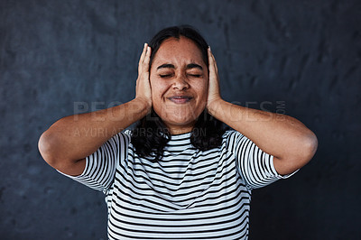 Buy stock photo Studio shot of a young woman covering her ears against a dark background