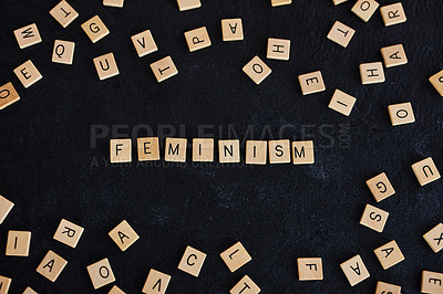 """Buy stock photo Studio shot of a wooden tiles with letters spelling out """"Feminism"""" against a black background"""