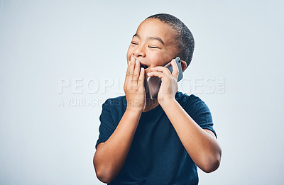 Buy stock photo Studio shot of a cute little boy looking amazed while using a smartphone against a grey background