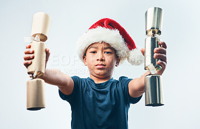 Buy stock photo Studio shot of a cute little boy wearing a Santa hat and holding two Christmas crackers against a grey background