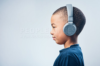 Buy stock photo Studio shot of a cute little boy using headphones against a grey background