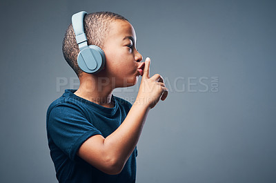 Buy stock photo Studio shot of a cute little boy using headphones and putting his finger on his lips against a grey background
