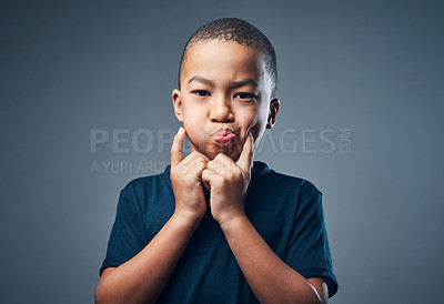 Buy stock photo Studio shot of a cute little boy making funny faces against a grey background