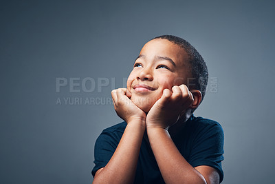 Buy stock photo Studio shot of a cute little boy looking thoughtful against a grey background