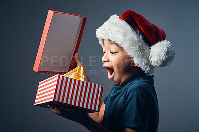 Buy stock photo Studio shot of a cute little boy opening a Christmas present against a grey background