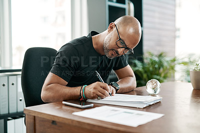 Buy stock photo Shot of a mature businessman filling out paperwork at his desk in a modern office
