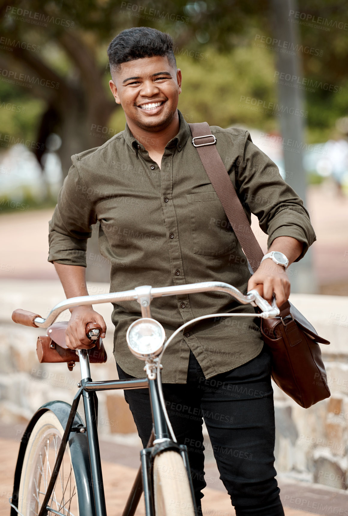 Buy stock photo Shot of a young businessman riding a bicycle in the city