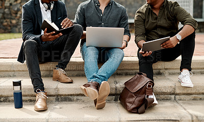 Buy stock photo Shot of a group of businessmen sitting on stairs and using a laptop during a meeting against a city background