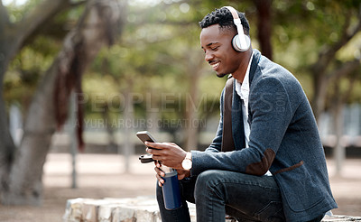 Buy stock photo Shot of a young businessman using a smartphone and headphones in the city