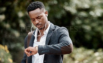 Buy stock photo Shot of a young businessman checking the time while walking through the city